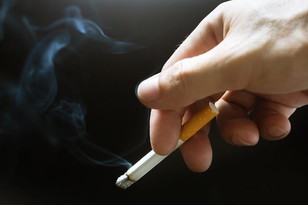 Uomo che tiene in mano una sigaretta fumante. diffusione del fumo di sigaretta.