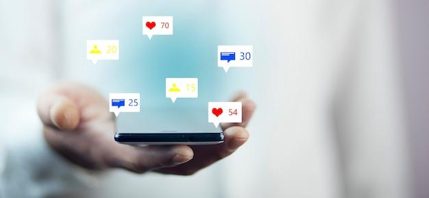 Uomo che tiene le icone dei social media con smart phone