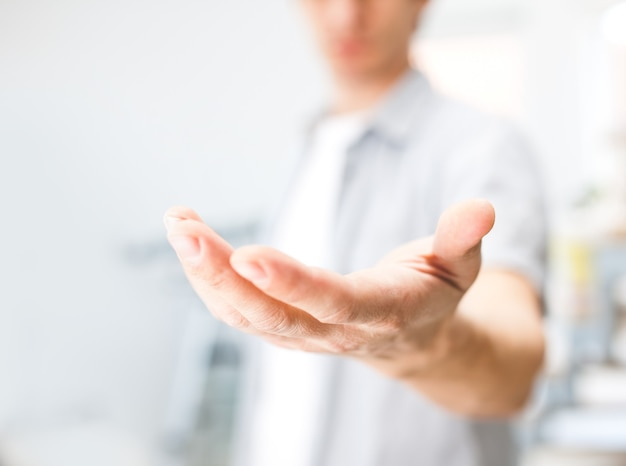 Uomo che tiene qualcosa sulla sua mano