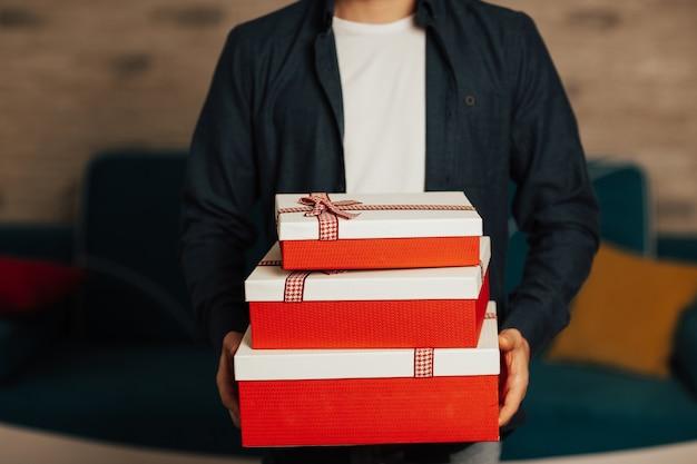 Uomo che tiene una pila di regali. ha in mano tre scatole regalo rosse pronte per san valentino.