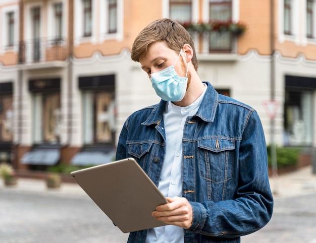 Uomo che tiene una compressa mentre indossa una maschera medica