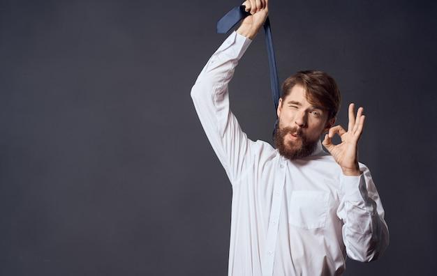 Uomo che tiene la cravatta in mano e soffocamento suicidio sfondo grigio modello vista ritagliata