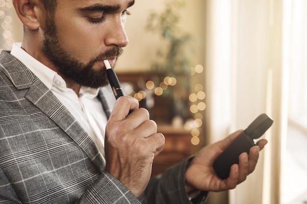 Uomo che tiene un sistema di riscaldamento del tabacco nelle sue mani