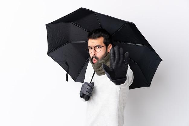 Uomo che tiene un ombrello sopra la parete isolata