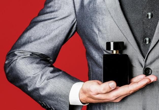 Uomo che sostiene una bottiglia di profumo. gli uomini profumano in mano sullo sfondo della tuta. odore di fragranza
