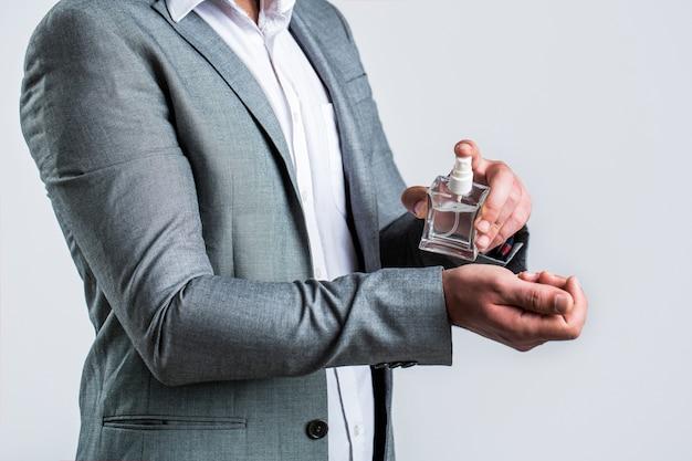 Uomo che sostiene una bottiglia di profumo.