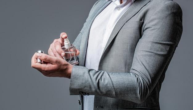 Uomo che sostiene una bottiglia di profumo