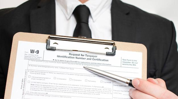 Uomo che tiene il modulo fiscale statunitense w-9. forma fiscale documento di legge irs concetto aziendale