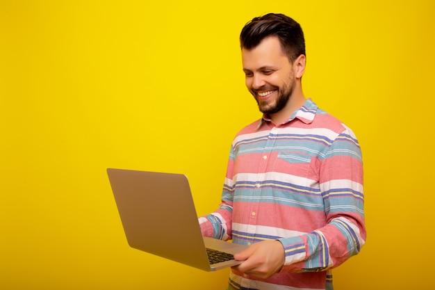 Uomo che tiene e utilizzando laptop.