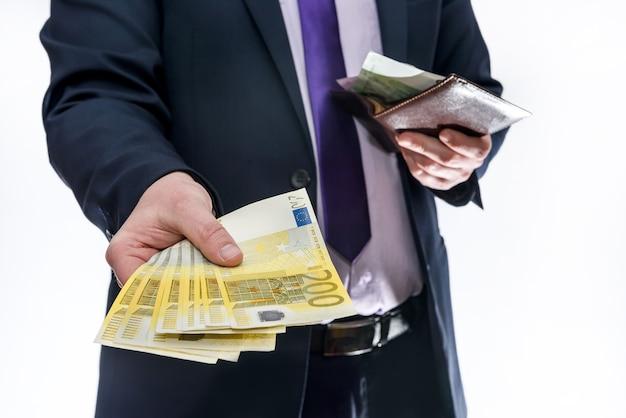Uomo che tiene il portafoglio e che offre banconote in euro