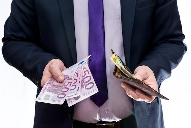 Uomo che tiene il portafoglio e offre banconote in euro