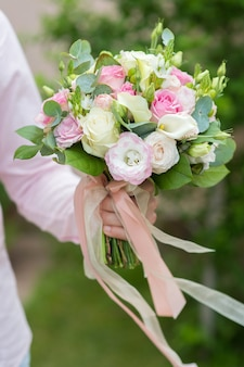 Un uomo con un bouquet da sposa in mano su uno sfondo di erba verde