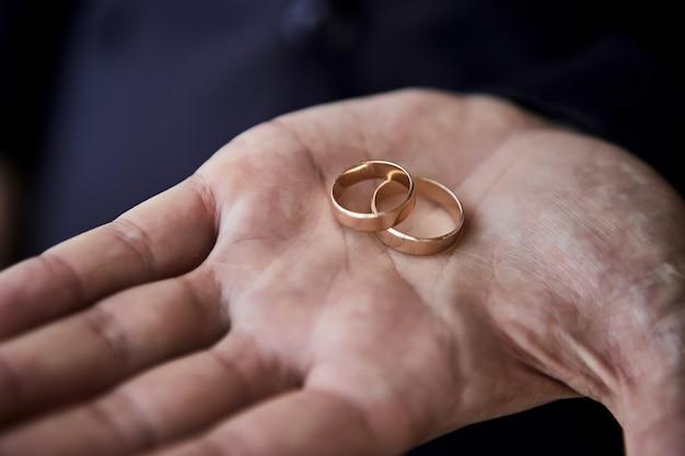 Uomo che tiene gli anelli di nozze, lo sposo si prepara la mattina prima della cerimonia