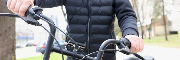 Uomo che tiene la ruota della bicicletta all'aperto primo piano