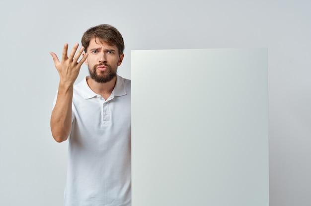 Uomo che tiene la parete isolata pubblicità di presentazione del modello bianco.
