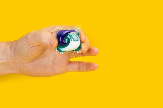 Uomo che tiene con le dita un baccello di detersivo per lavatrice su sfondo giallo