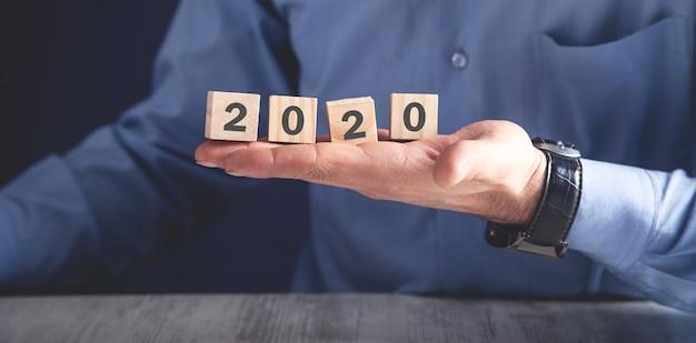 Uomo che tiene i cubi di legno con l'anno 2020.