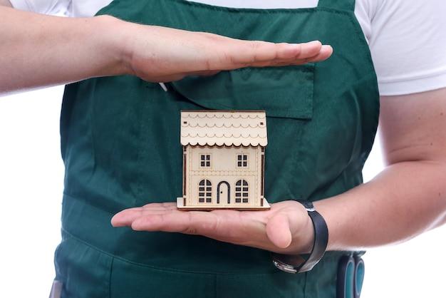 Uomo che tiene il modello di casa in legno sul palmo