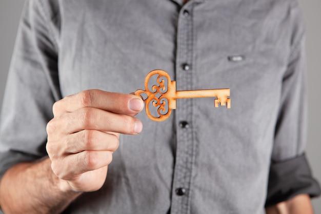 Uomo che tiene una chiave di legno su sfondo grigio