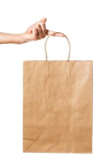 L'uomo tiene un sacchetto di carta isolato su sfondo bianco prodotto biodegradabile