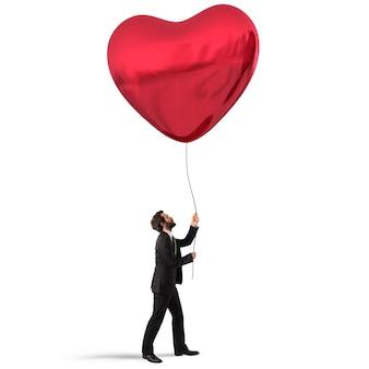 L'uomo tiene in mano un grande palloncino a cuore rosso
