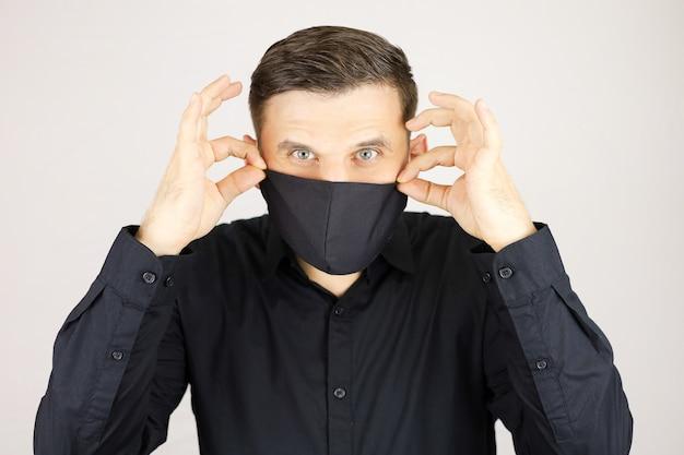 Un uomo tiene una maschera medica nera su sfondo bianco