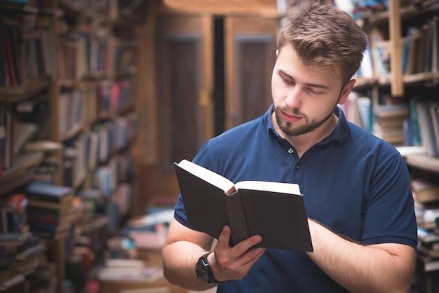 L'uomo tiene in mano un libro e lo legge in una biblioteca pubblica