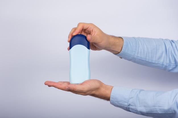 L'uomo tiene la bottiglia di shampoo o balsamo su sfondo bianco. copia spazio, mock up