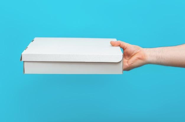 Un uomo tiene le scatole nelle sue mani su uno sfondo blu. servizio di consegna delle merci. servizio di consegna in città.