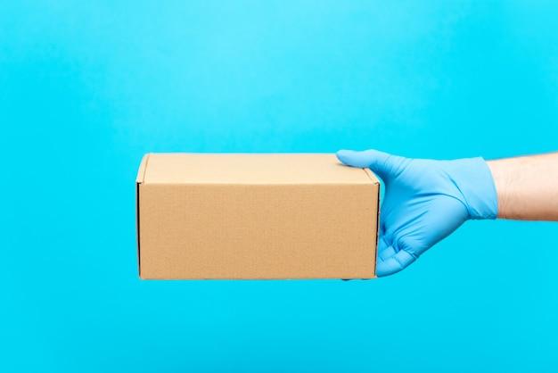 Un uomo tiene una scatola di cartone con la mano in un guanto di gomma. protezione contro covid-19. consegna sicura delle merci durante l'epidemia di coronavirus.