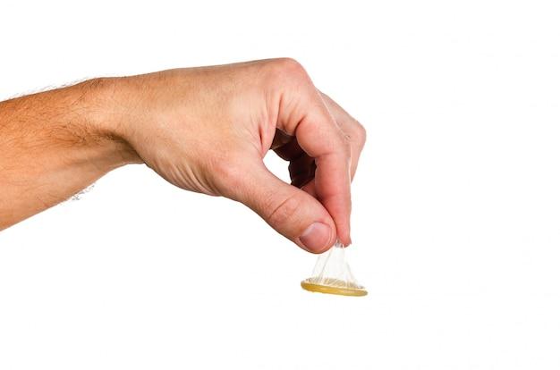 L'uomo tiene un preservativo dalla cima con due dita.