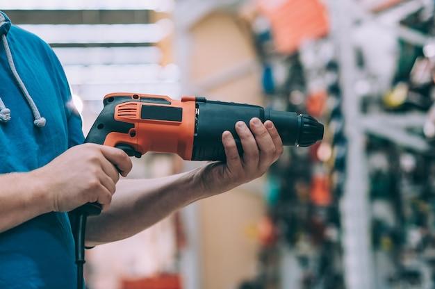 Un uomo tiene in mano un trapano elettrico per la perforazione