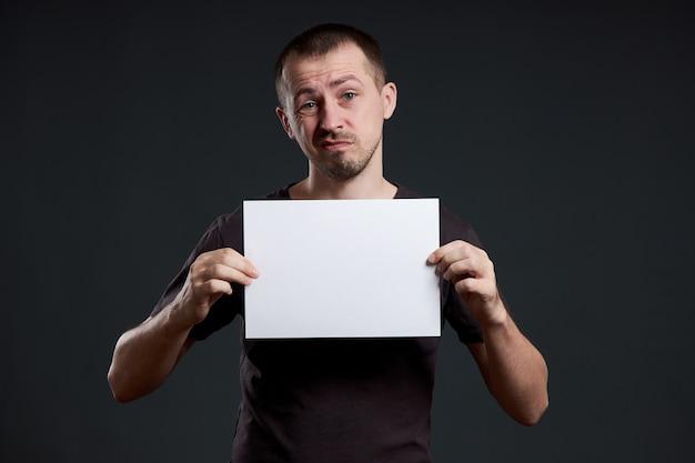 L'uomo tiene un foglio di carta poster vuoto nelle sue mani. sorriso e gioia, posto per il testo, copia dello spazio