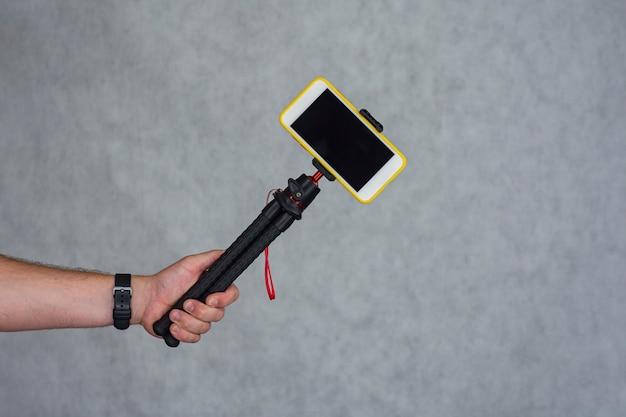 Un uomo tiene un treppiede flessibile con un modello di uno smartphone con uno schermo nero.