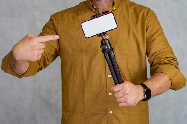 Un uomo tiene un treppiede flessibile con un modello di uno smartphone con uno schermo bianco.