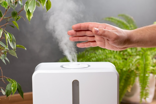 L'uomo tiene la mano sul diffusore di olio aromatico a vapore a casa