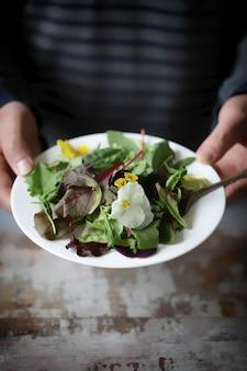 Un uomo tiene un'insalata sana.