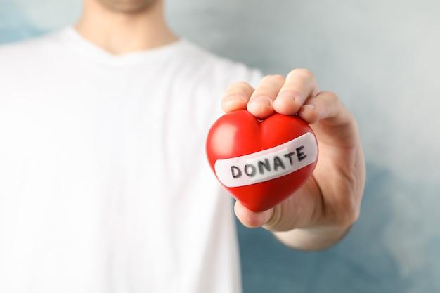L'uomo tiene il cuore su spazio blu, da vicino. assistenza sanitaria, donazione di organi