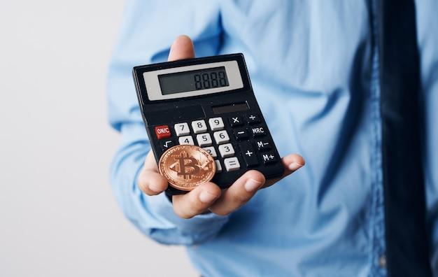 Un uomo tiene nelle sue mani una tecnologia finanziaria del calcolatore di aumento del prezzo di criptovaluta bitcoin.