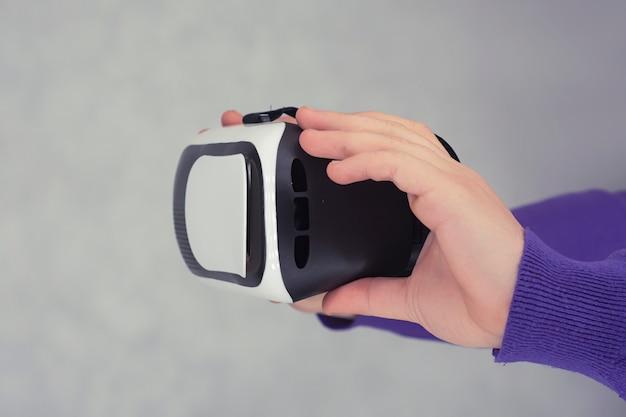 L'uomo tiene in mano gli occhiali per la realtà virtuale e il video a 360 gradi. casco vr per smartphone su sfondo chiaro.