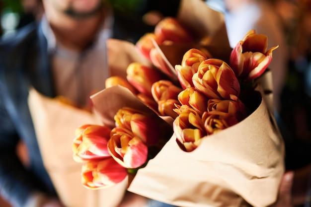 L'uomo tiene tra le mani diversi mazzi di tulipani rossi gialli da presentare a una donna.