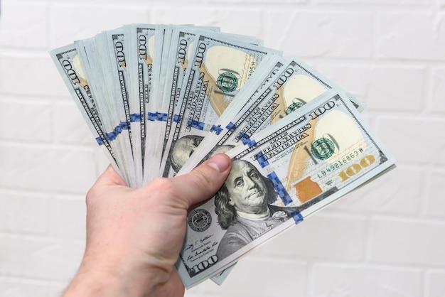L'uomo tiene centinaia di denominazioni di dollari isolati su sfondo bianco