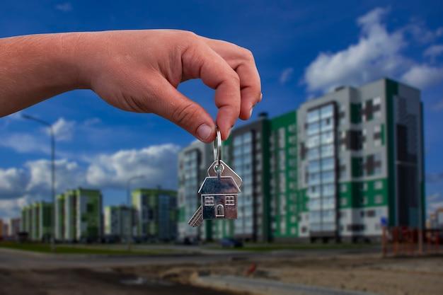 L'uomo tiene in mano le chiavi di casa sullo sfondo di un edificio a più piani. concetto per l'acquisto e l'affitto di appartamenti.