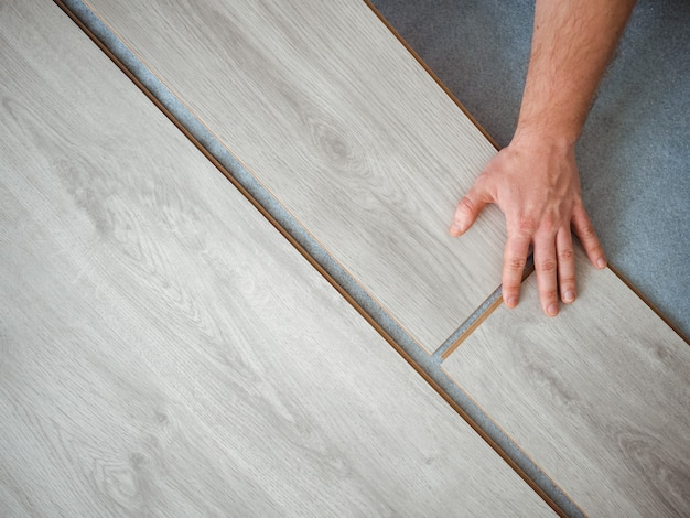 Un uomo tiene in mano una tavola di laminato. il processo di riparazione nella stanza