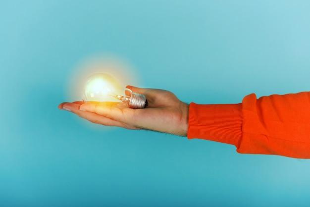 L'uomo tiene in mano una lampadina sul ciano