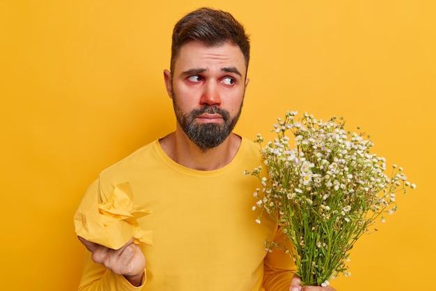 L'uomo tiene il tovagliolo e il bouquet di camomilla soffre di allergia vestito casualmente isolato su giallo