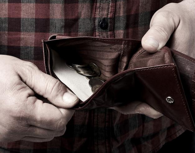 L'uomo tiene un portafoglio in pelle marrone aperto con monete grivna ucraina, concetto di povertà