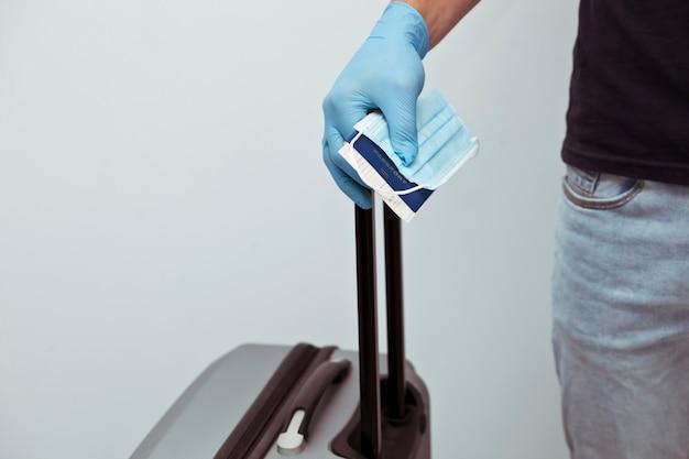 L'uomo tiene il passaporto con il biglietto del treno e la mascherina medica in mano indossando guanti in lattice