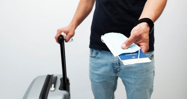L'uomo tiene il passaporto con il biglietto del treno e la mascherina medica
