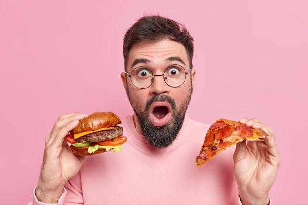 L'uomo tiene un pezzo di pizza e un hamburger mangia cibo spazzatura scioccato dal consumo di molte calorie indossa occhiali rotondi maglione casual